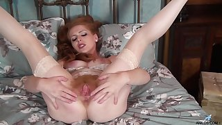 Adorable redhead chick Tia Jones drops her white panties to posture